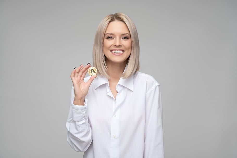 Frau hält Bitcoin Münze in der Hand