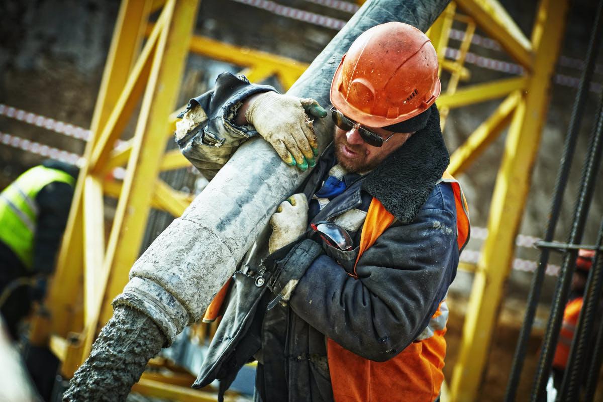 Bauarbeiter mit Betonschlauch